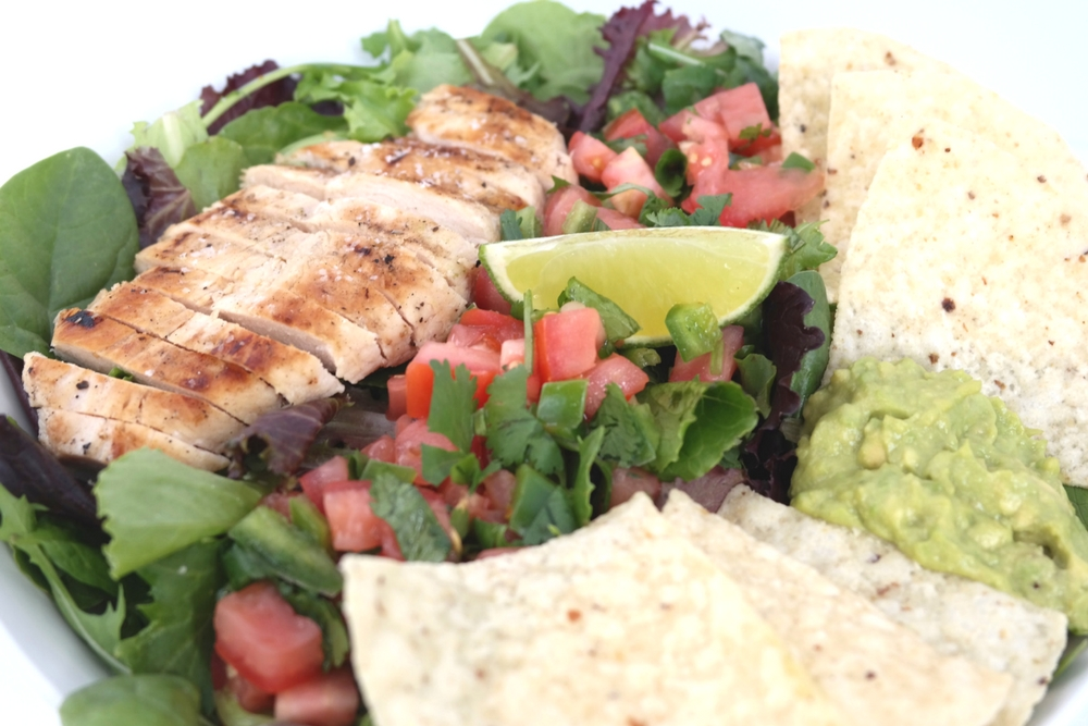 Margarita Chicken Salad is fresh and a bit fiery! Chicken breast marinated in margarita mix, guacamole, and a spicy Pico de gallo atop a blend of greens